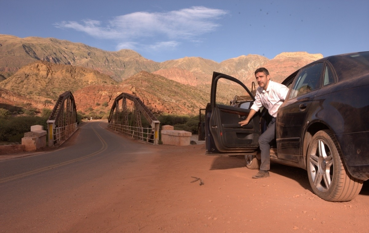выходит из машины в пустыне
