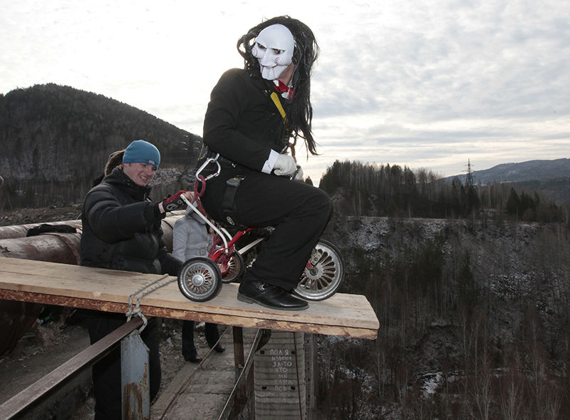 A man, dressed in a Halloween costume, prepares before taking a rope jump from a 44 metre high (144 feet high) old water pipe bridge in the Siberian Taiga area outside Krasnoyarsk October 28, 2012. Enthusiasts take rope jumps ahead of the Halloween celebrations. REUTERS/Ilya Naymushin (RUSSIA - Tags: SOCIETY)