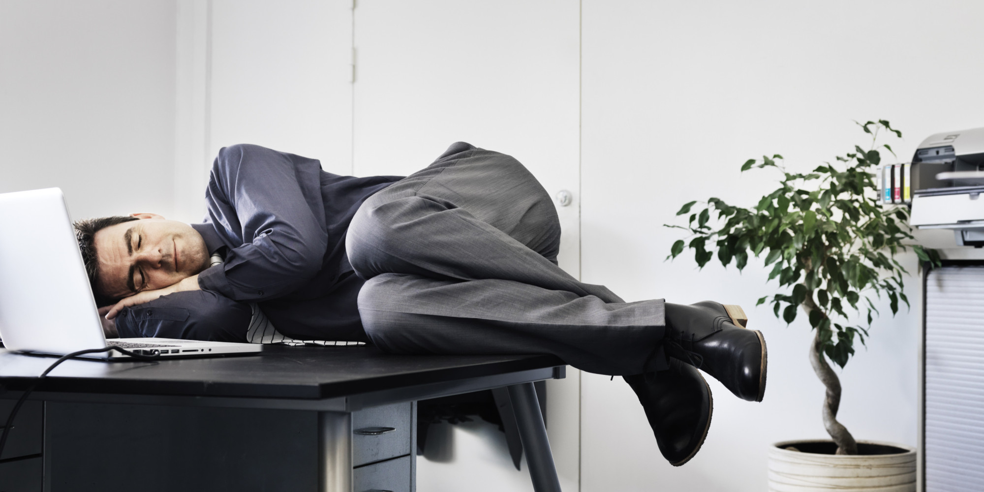 Businessman asleep on his office desk