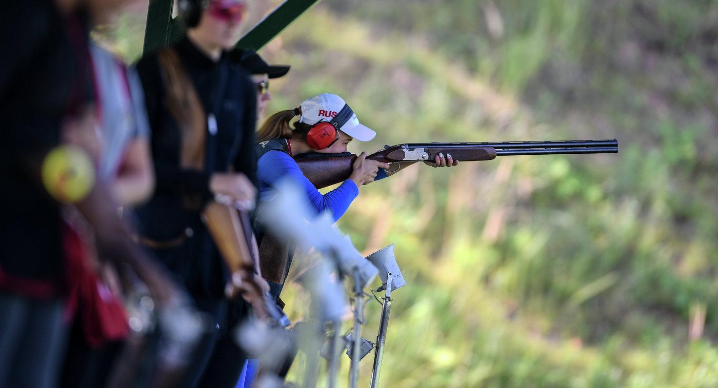 девушка стреляет по тарелкам из ружья